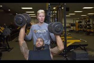 Man lift weights, being spotted by another person.